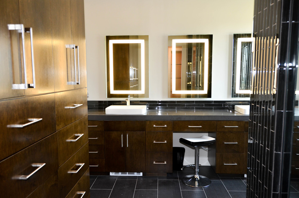 Modern master bathroom with dark wood and self-lit vanity mirrors
