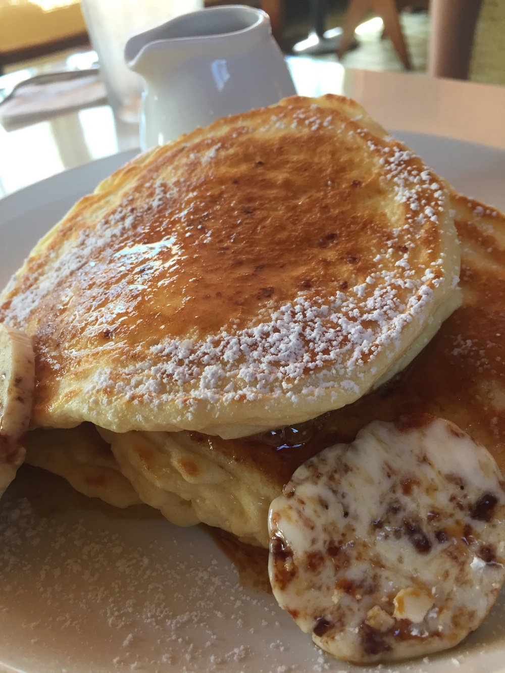 Ricotta hotcakes, banana, honeycomb butter, served with a jug of syrup and dusted with icing sugar