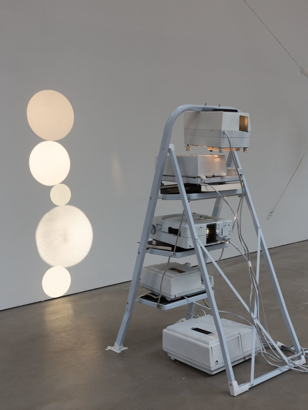 Fünf Monde , 2015  5 slide projectors and household ladder  102 × 45 × 75 cm   Unique