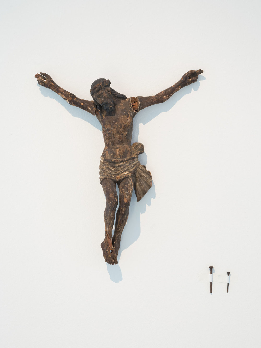 Ein Nagel tut's auch , 2015  Wood, 2 nails  Jesus:  47 × 42 × 9,5 cm (18 ½ × 16 ½ × 3 ¾ inches)  Nail 1: 6,5 cm   Nail 2: 5 cm   Unique