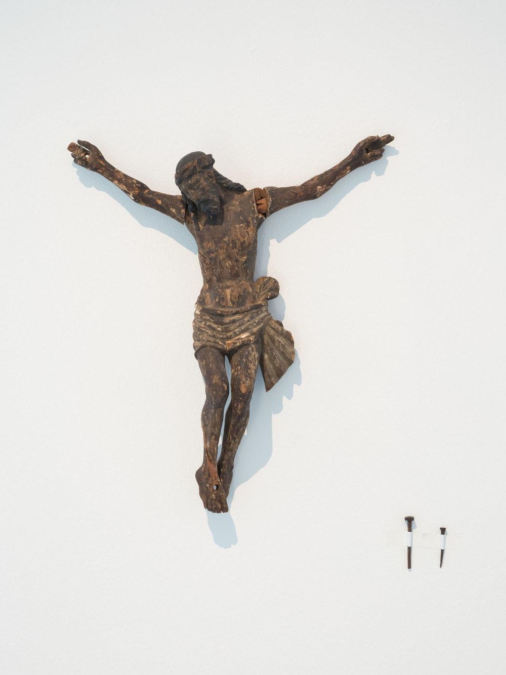 Ein Nagel tut's auch , 2015  Wood, 2 nails  Jesus:  47 × 42 × 9,5 cm (18 ½ × 16 ½ × 3 ¾ inches)  Nail 1: 6,5 cm  Nail 2: 5 cm  Unique