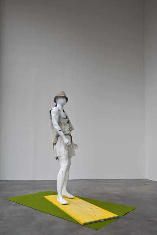 Sigalion (Angerone, Harpocrates) , 2013  mannequin, felt, acrylic, stamp  Mannequin : 194 × 50 × 49 cm  Frühlingswiese Modelbau Rasen: 200 × 100 cm  Glass sheet: 36 × 36 cm