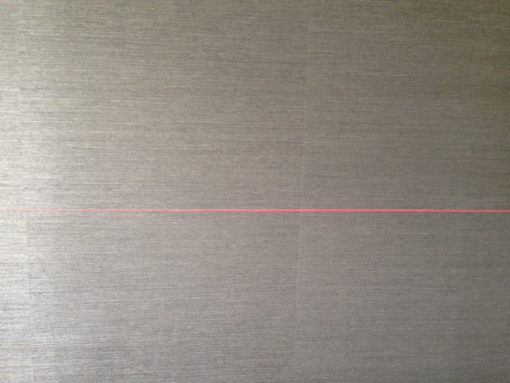 Day-Glo pink laser marking a level line for the future location of the buffet on bronze-grey grasscloth. Color combo was perfection.