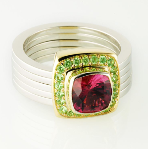 Renaissance ring of a cushion pink tourmaline surrounded by green garnets