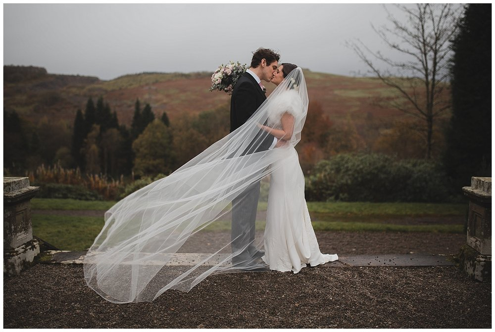 Bride and groom kissing while a long veil blows across them at their Auchen Castle wedding in Scotland.