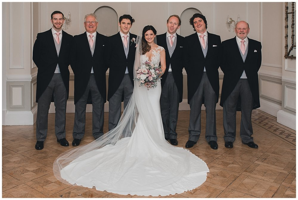 Bride, groom and ushers showing off the train on brides Pronovias dress.