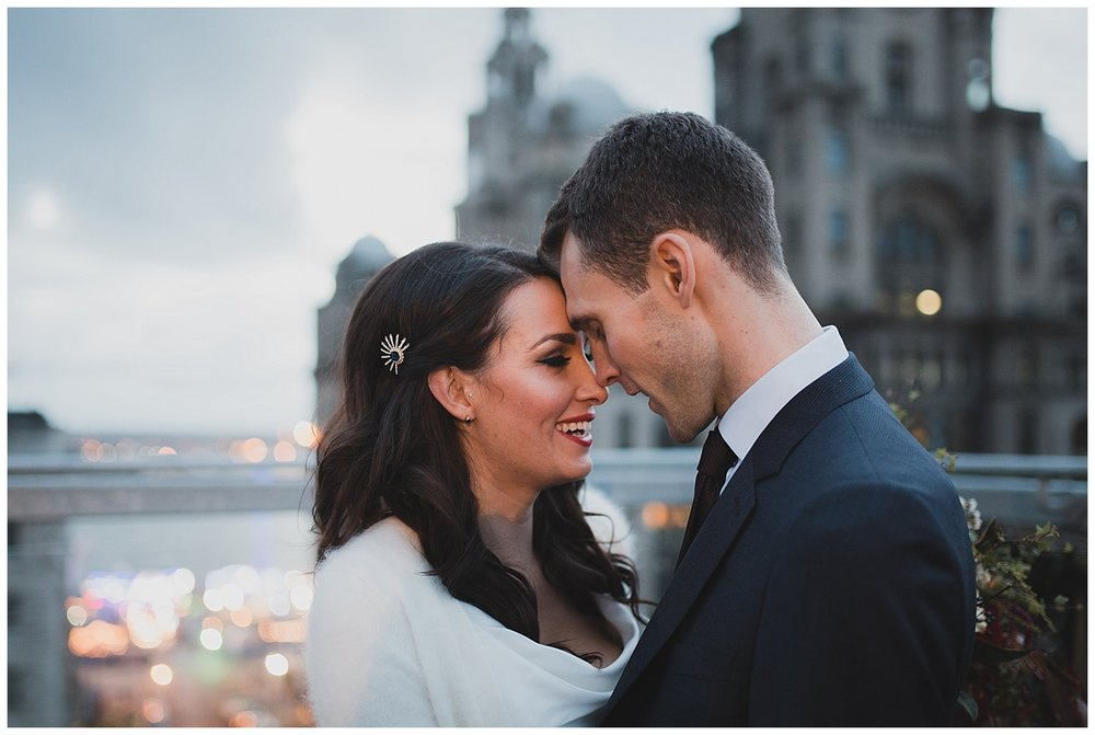 Bride and Groom on the roof terrace at Oh Me Oh My Liverpool overlooking the Liver building.