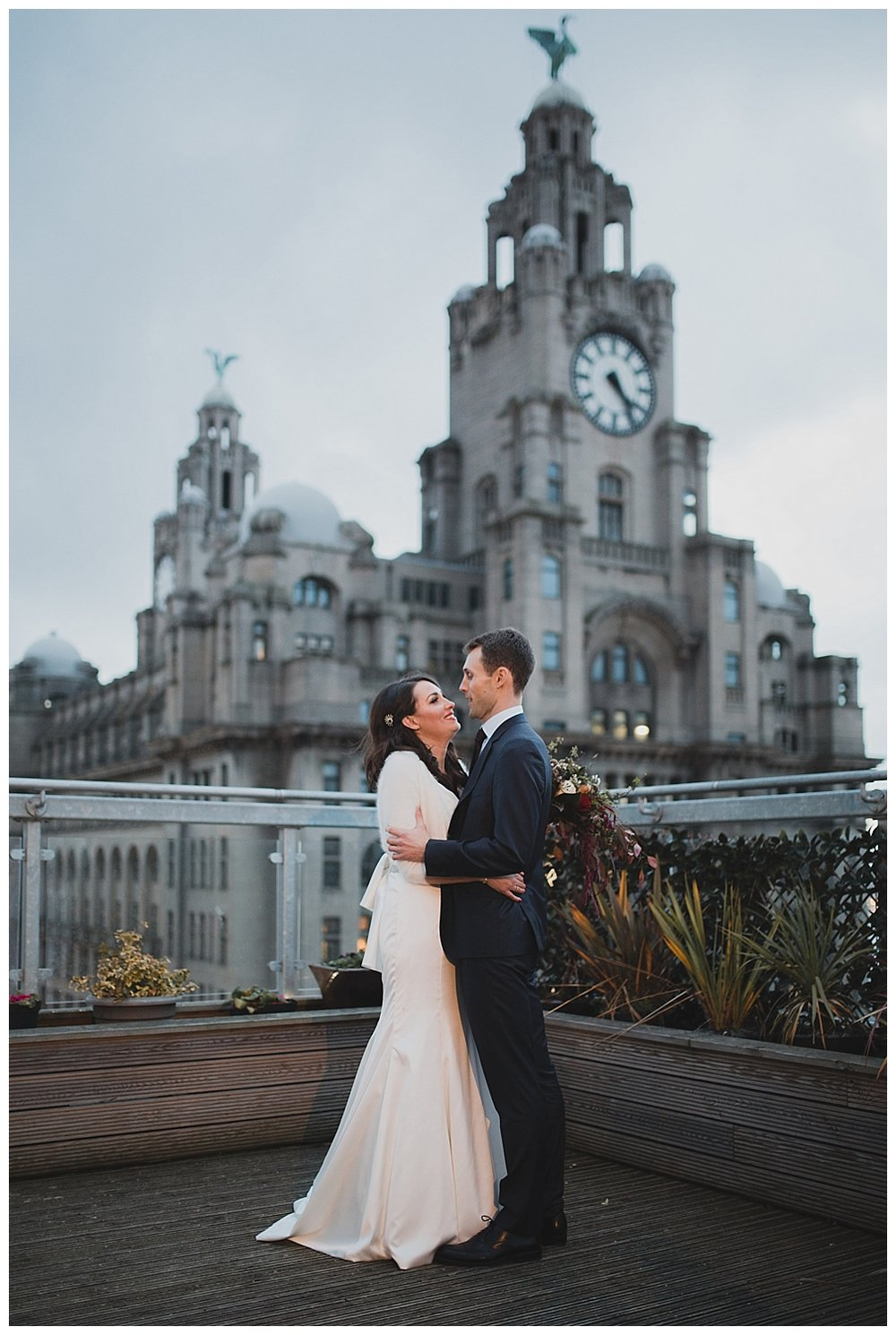 Bride and groom on the roof terrace at Oh Me Oh My Liverpool. The Liver building and Liver birds in the background.