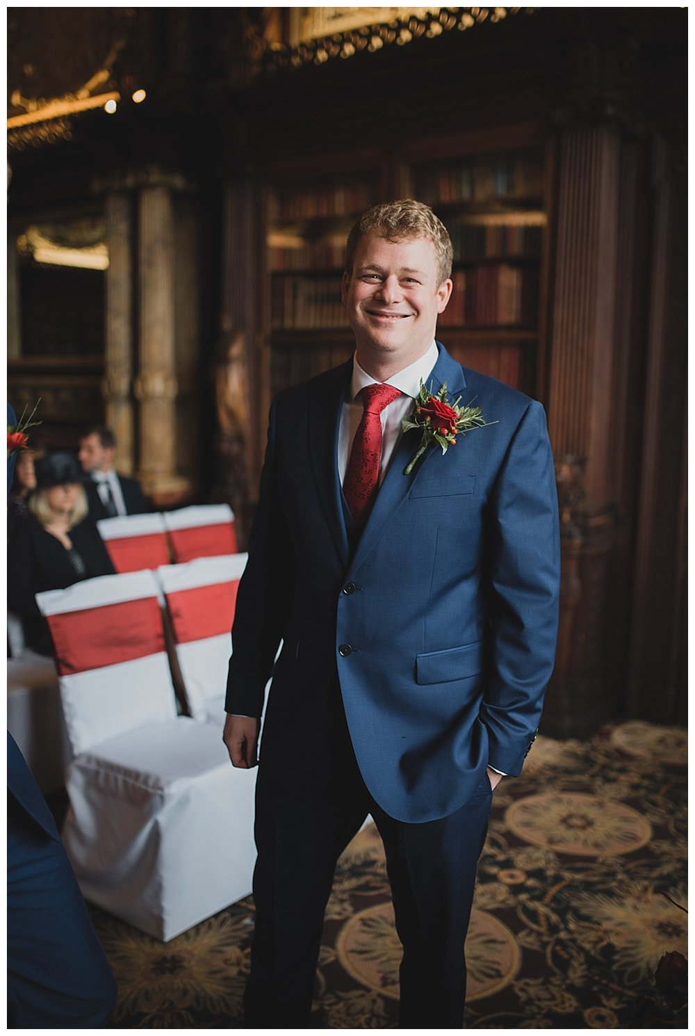 Navy suit and red buttonhole fro a Crewe Hall wedding.