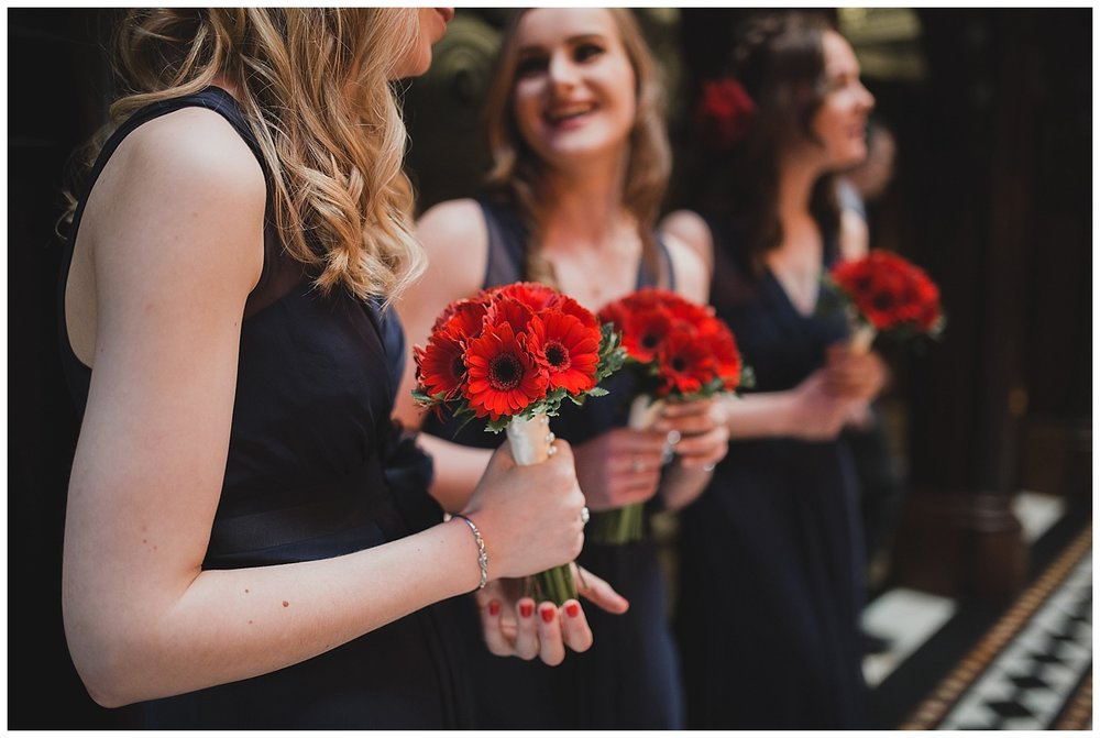Navy dresses and red bouquets for a Valentines themed wedding at Crewe hall in Cheshire