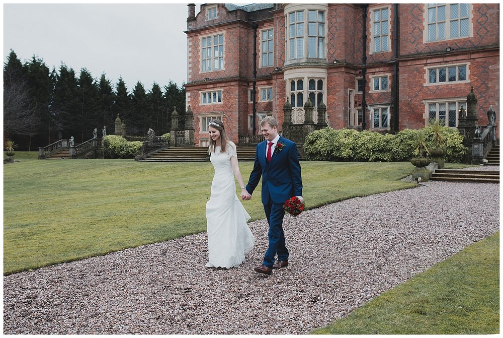Bride and groom walk in the grounds at Crewe Hall in Cheshire