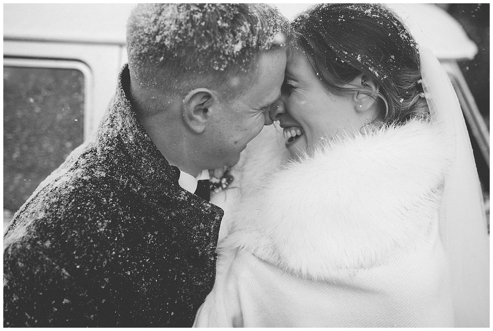 Bride and groom Eskimo kisses in the snow.