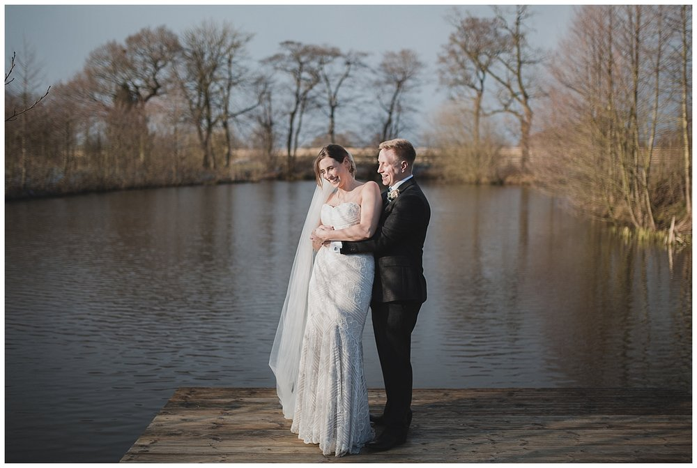Bride and groom at the lake at Styal Lodge in Cheshire