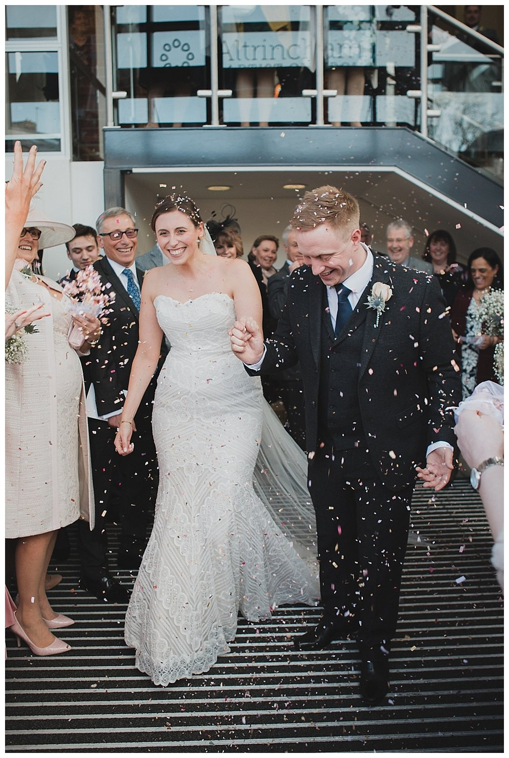 Bride and groom exit in a confetti storm at Altrincham Baptist Church.