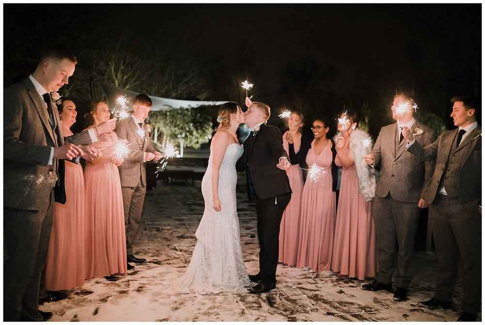 Bridal party with sparklers in the snow at Styal Lodge