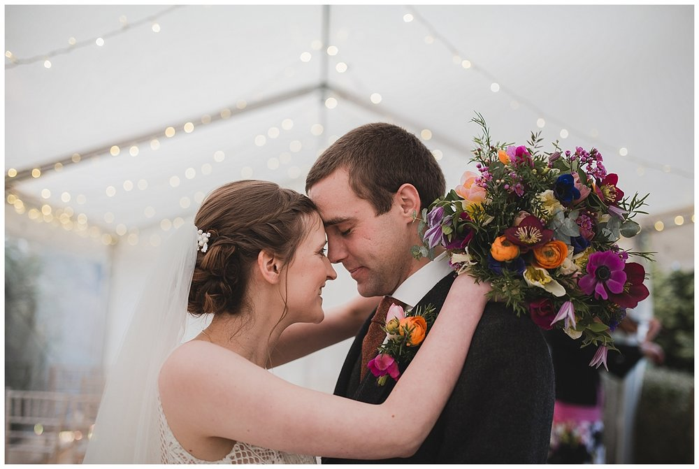 Bride and groom at their marquee wedding with bright spring bouquet.