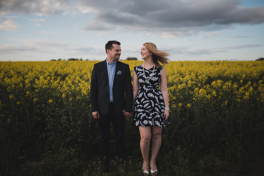 Engaged couple in a field of yellow.