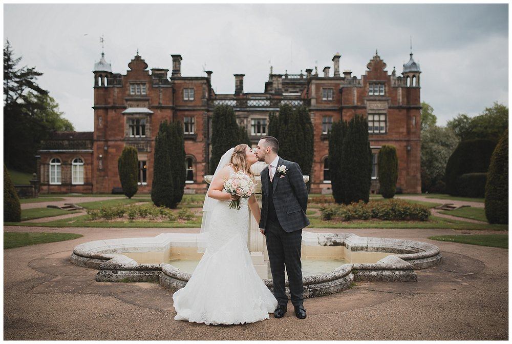 Bride and groom in front of the fountain at keele Hall in the Keele University grounds.