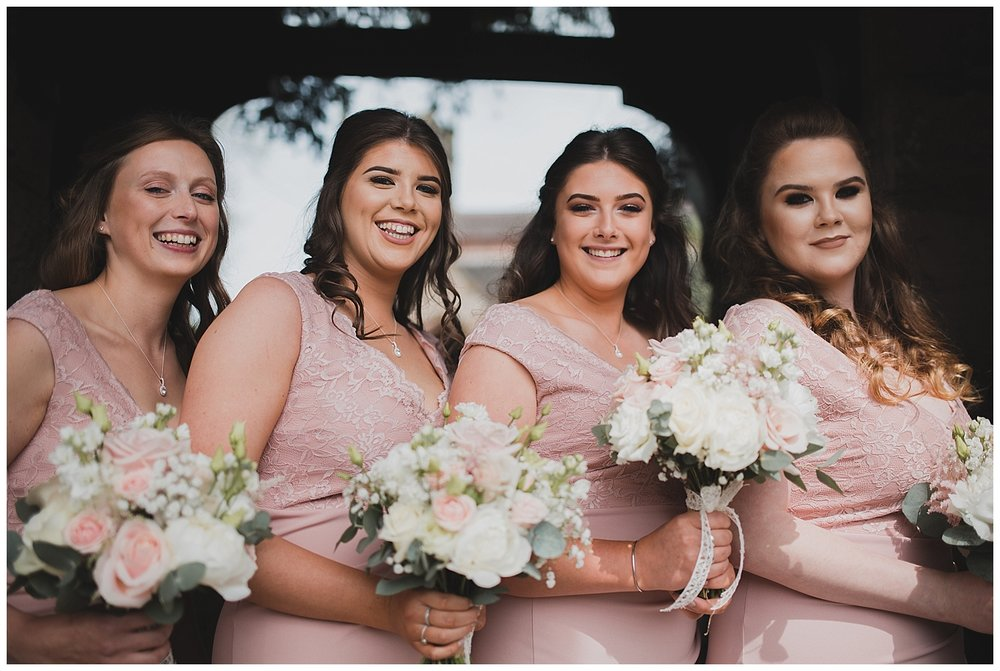 Bridesmaids outside the church in dusty pink dresses with pastel bouquets.
