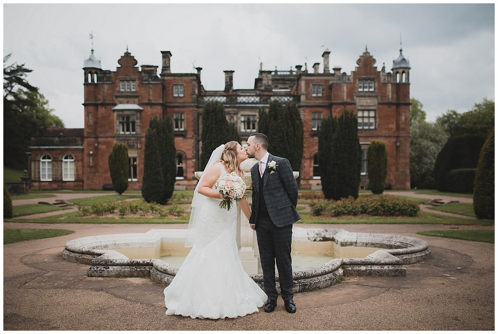 Bride and groom with the magnificent fountain at Keele Hall.