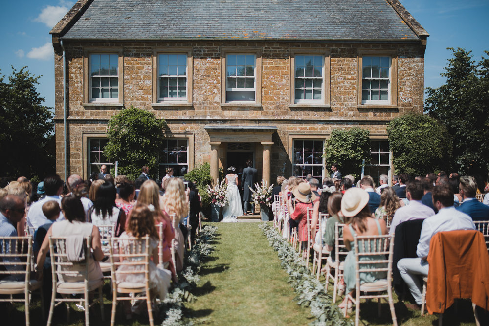 An outdoor summer wedding ceremony at Axnoller Farm in Dorset.