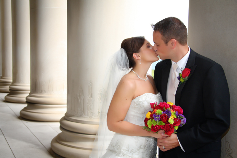 Bride and Groom kiss by pillars