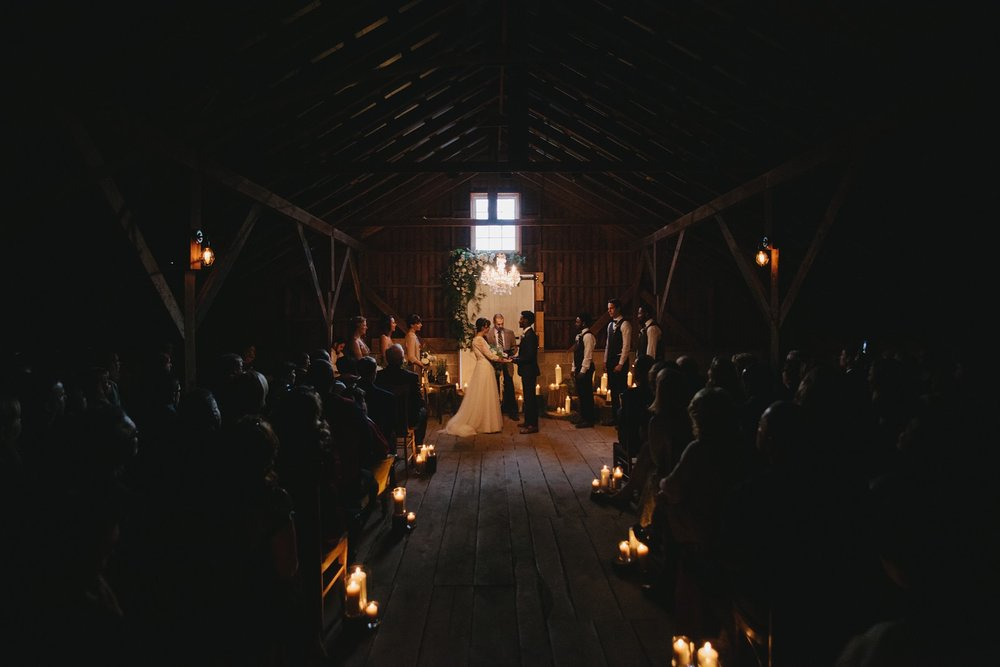 Romantic candlelit wedding ceremony in a barn with the bride and groom and wedding party