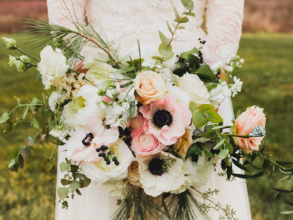 Natural white and pink winter wedding bouquet with anemones, roses and berries