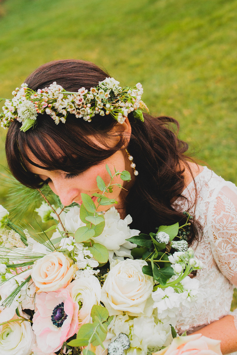 A bride wearing a simple floral crown with wax flower, lisianthus buds holding her bouquet with ranunuclus, anemones and eucalyptus pods