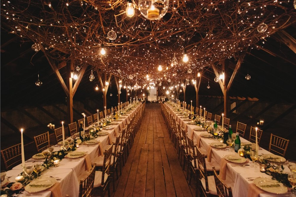 A romantic barn wedding with over the top twinkle lights, hanging candles, long tables and chiavari chairs