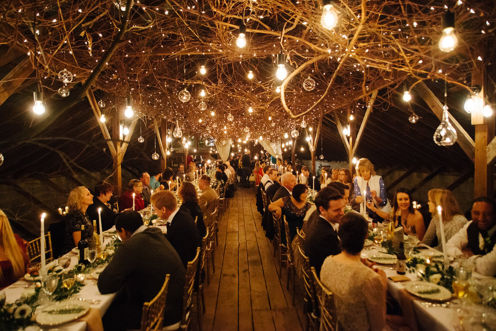 Barn Wedding guests happily eating at long tables with candles and twinkle lights above them