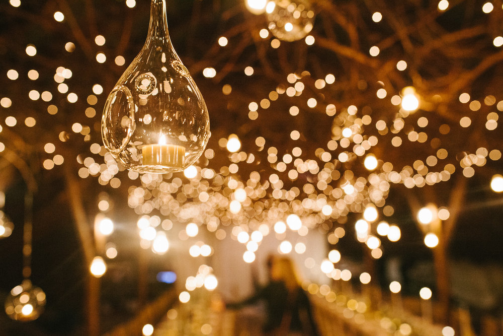 Hanging candles surrounded by twinkle lights at a winter barn wedding and reception