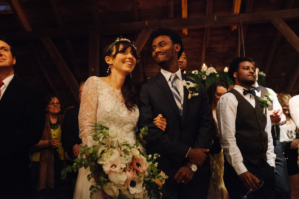 A black groom and white bride holding her bouquet and laughing happily at their barn wedding