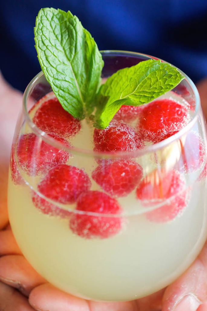 Photo via Damn Delicious  Described as the 5 minute cocktail, Damn Delicious highlights a few of our favorite things with their Raspberry Limoncello Prosecco sipper. Just combine and go!  Frozen raspberries act as ice cubes and the light sparkle of Prosecco gives this beverage a Bellini-esque playful vibe. Top with a few sprigs of mint - summer's unofficial herb - and you are ready to sit back, relax and chill out.
