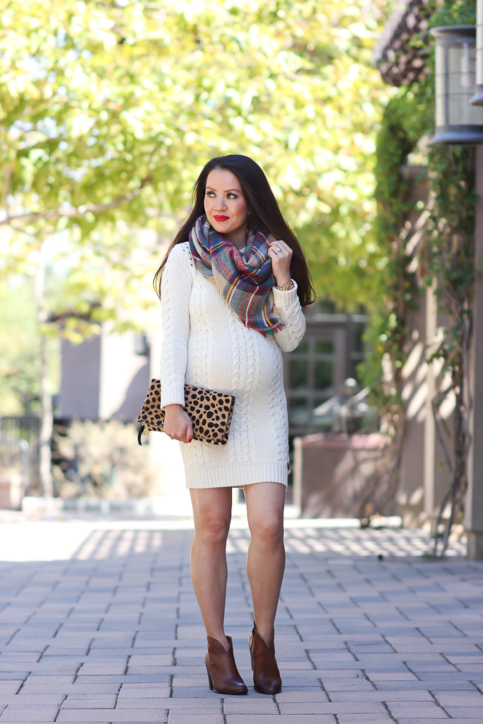 Image via Stylish Petite  Not only is the blanket scarf a big YES this season but a flannel pattern adds just the right amount of back to school prep for any ensemble. Annie of Stylish Petite rocks her blanket scarf tied as a side hankerchief and we love how the proportions and coverage on top balance her exposed stems and playful sweater dress. Kudos for showing off the adorable baby bump too!