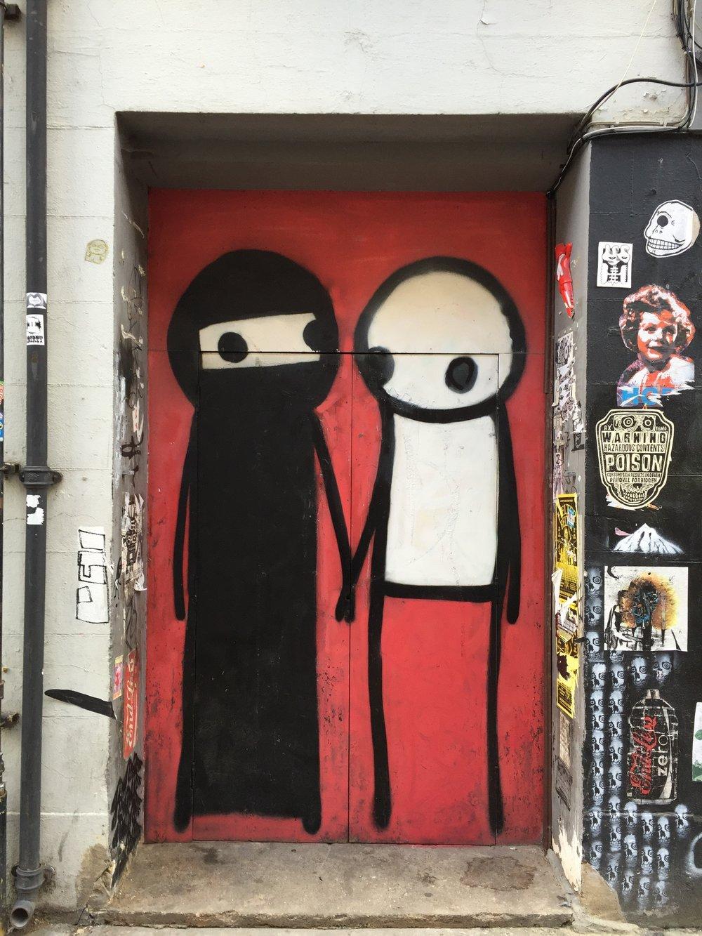 Mural painted in doorway down Princelet Street off of Brick Lane, London. Photographed by Reem Gallery in autumn 2016.