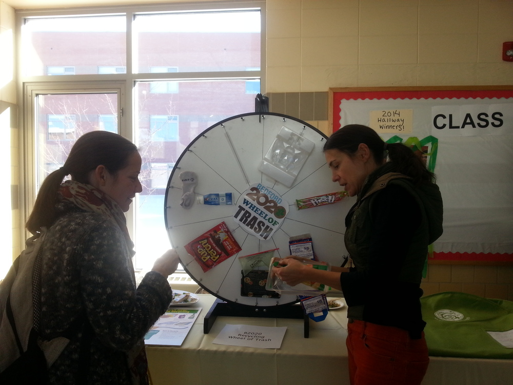 "Veronique Pittman of the Bedford2020 Board spins the ""Wheel of Trash"" with a participant. The Wheel of Trash is an interactive educational tool to inform the public about commonly trashed items that are actually recyclable."