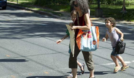 Danielle Meitiv walks home with her children Rafi, 10, left and Dvora, 6, right. (AP Photo/Jose Luis Magana)