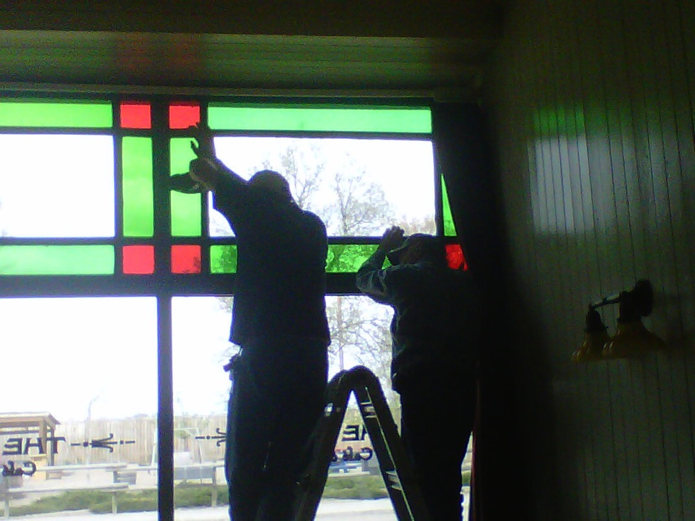 Installing the repaired transom windows.