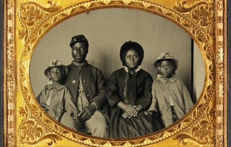 Quarter-Plate Ambrotype taken between 1863 and 1865. Image depicts a Black Union Army private and his wife and twin daughters.