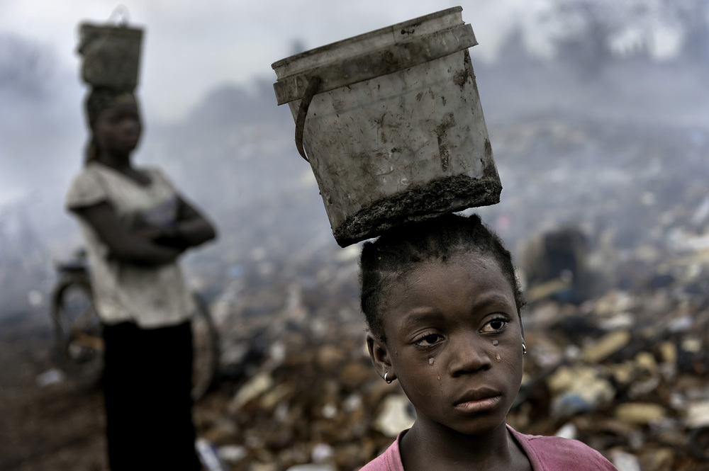 Working to Survive © Renée C. Byer In an e-waste dump that kills nearly everything that it touches in Ghana, West Africa, Fati, 8, works with other children searching through hazardous waste in hopes of finding whatever she can to exchange for pennies in order to survive. While balancing a bucket on her head with the little metal she has found, tears stream down her face as the result of the pain that comes with the malaria she contracted some years ago. This is work she must do to survive.