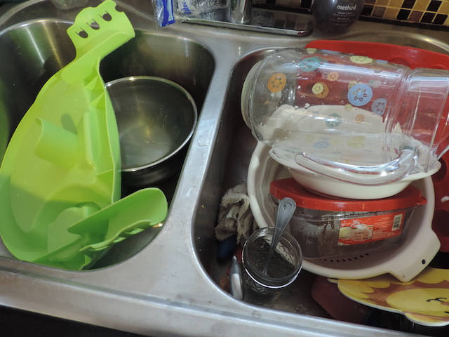 kitchen sink piled with dishes speed cleaning your kitchen