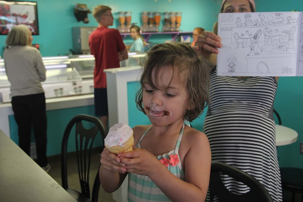 """Our middle kiddo enjoys her ice cream cone inside the Island Creamery, while Joanna holds up the """"Inside the Creamery"""" page of her book."""