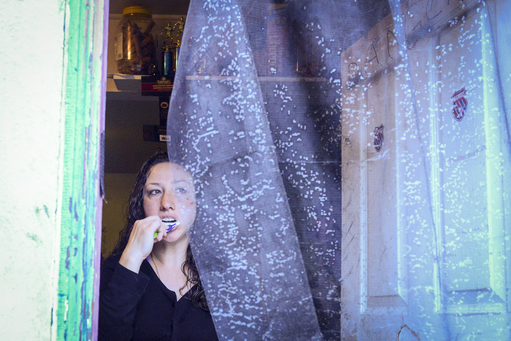 Amanda brushes her teeth while getting ready to go to work. She does not have running water in her home.