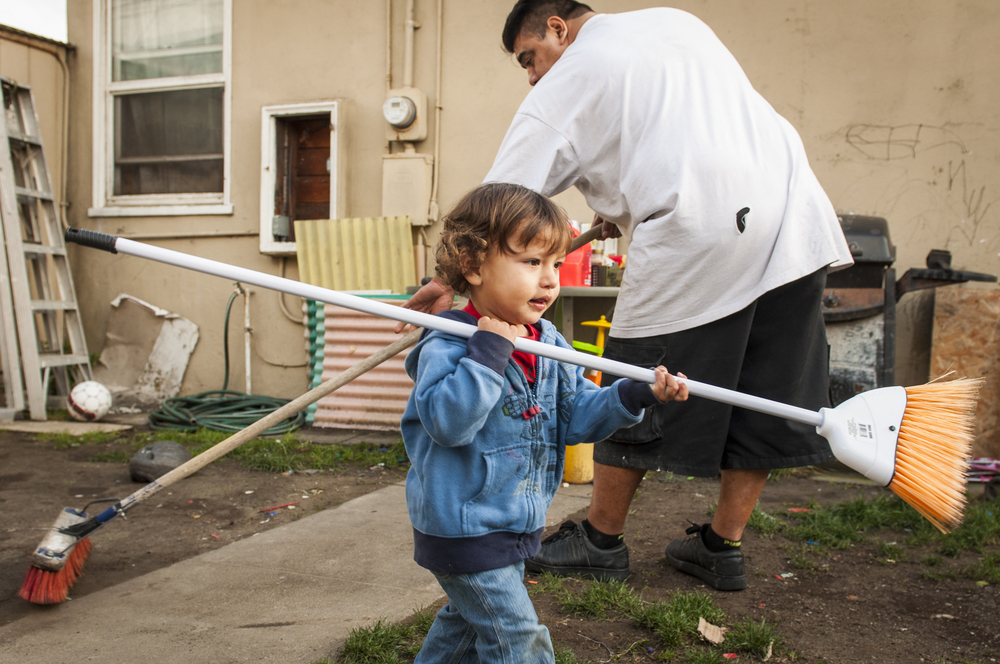 Dominic and his father Felipe clean the back yard.