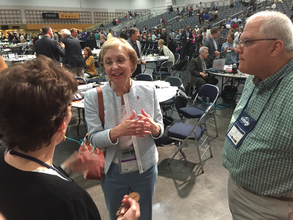 Bishop Janice Riggle Huie talks with rio texas delegation members Laura merrill and abel vega during a break in Wednesday's proceedings.