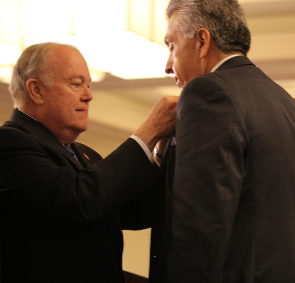 Bishop Mike McKee pins an episcopal pin to Bishop Saenz.