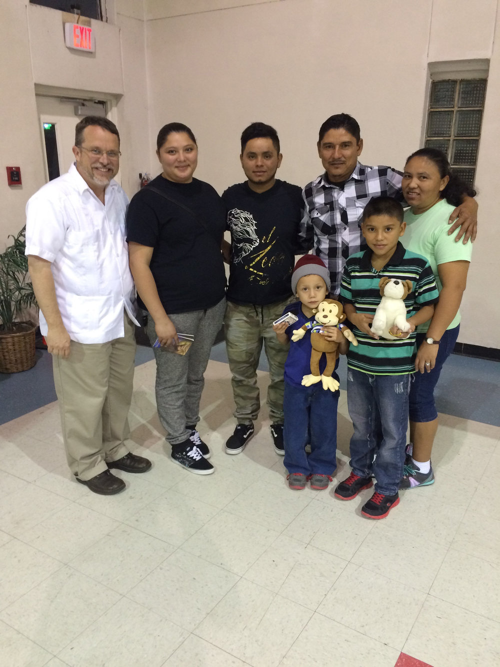 The Rev. John Feagins (far left) with a woman and her two young sons who were reunited with her husband and other children at La Trinidad United Methodist Church in San Antonio, Texas. Photo: Courtesy John Feagins