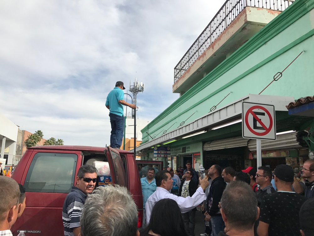 Arriving at a street corner in Nuevo Laredo with water to share, a pastor with the Baptist church network offers a blessing and prayer for the Cuban migrant community congregating in the streets.