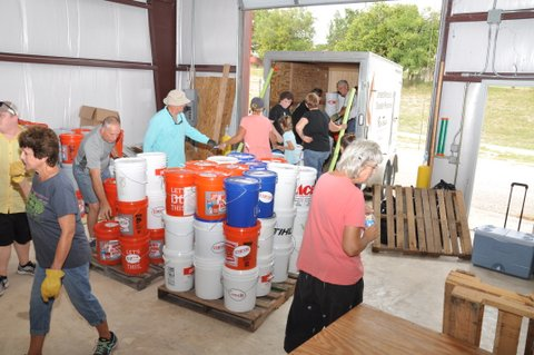 Volunteers load flood buckets into trailers at the disaster response warehouse in Kerrville.